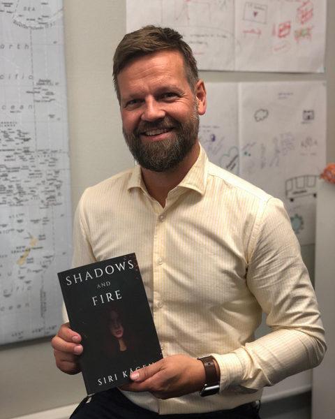 """Rektor Endre Helsem holder boken """"Shadows and Fire"""" av Akademeitelev Siri Kågen. Foto."""