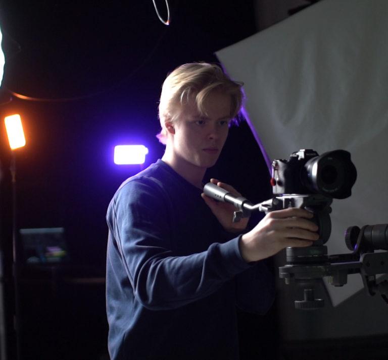 Elev med kamera i mørkt studio. Foto.