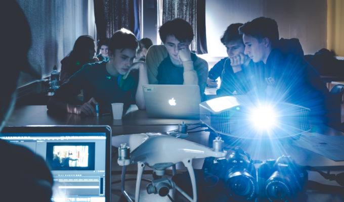 Elever som arbeider med medieproduksjon rundt et bord.