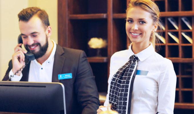 Fagbrev i salgsfaget. En mann og en kvinne som arbeider i hotellresepsjon. Foto.